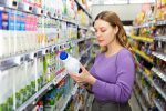 Portrait of young woman customer choosing milk and dairy products in grocery